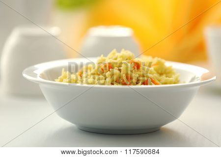 Stewed rice with a carrot in a white bowl on a table, close up