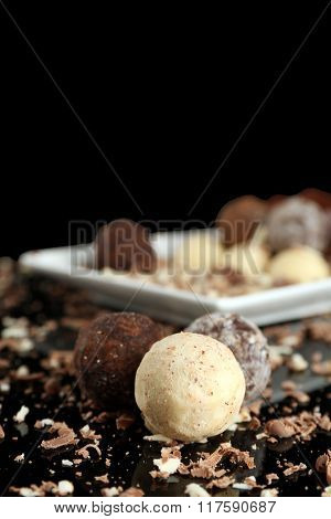 Assorted chocolate candies with flakes on black background