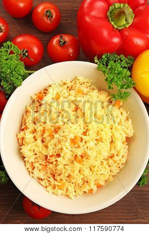 Stewed rice with a carrot on a plate over wooden background, close up