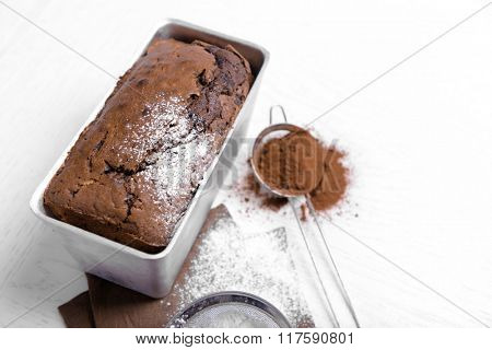 Chocolate cake in baking dish with cocoa powder on white table