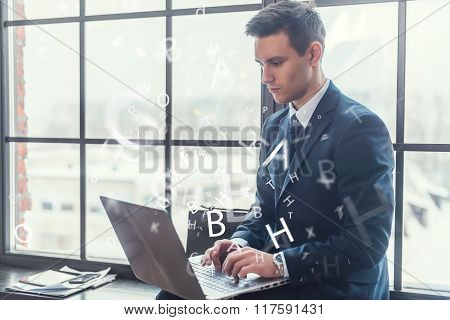 Businessman working on his laptop keyboarding net-book