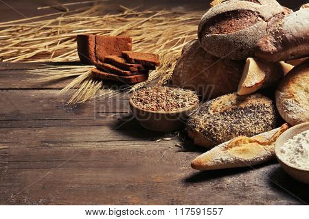 Fresh baked bread, flour and wheat on the wooden background