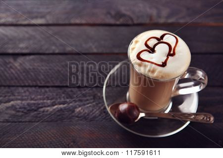 Milk coffee in glass cup with chocolate syrup on black wooden table