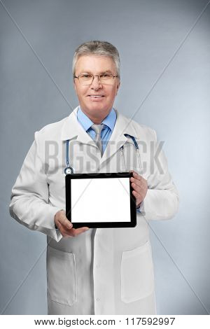 A handsome doctor with stethoscope and tablet standing on grey background