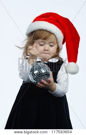 little girl with mirror ball and santa hat