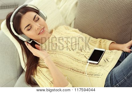 Happy young woman with headphones listening to music on a sofa at home