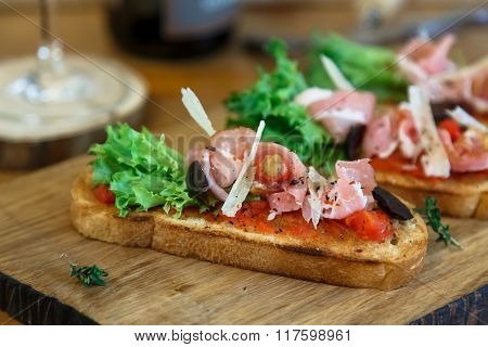 Tapas On Crusty Bread - Selection Of Spanish Tapas Served With A Sliced Baguette.