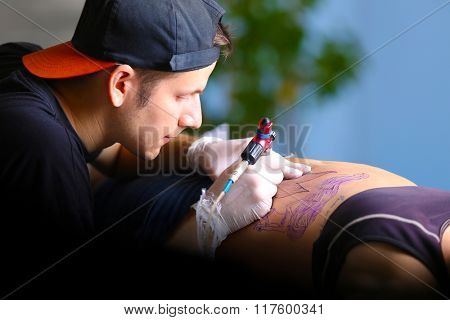 Tattooist makes tattoo, close up