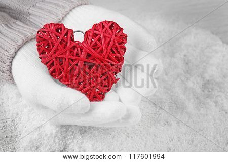 Hands in warm white gloves holding red heart on snowy background