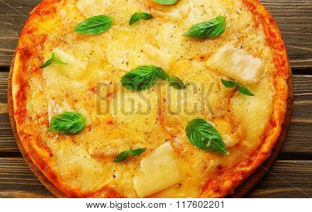 Tasty pizza decorated with basil  on wooden background, close up