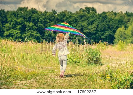 little cute girl flying a kite in a meadow on a sunny day, back view