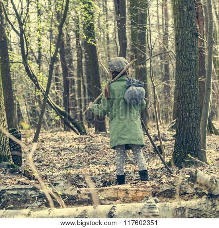 little girl goes through the woods. back view