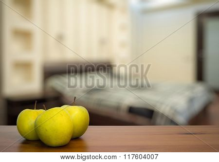 green apple on wooden table in the bedroom