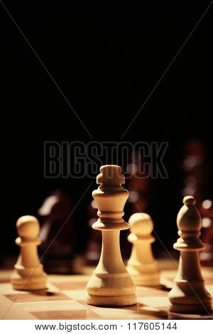 Chess pieces and game board on black background