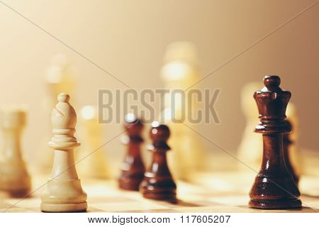 Chess pieces and game board on soft blurred background