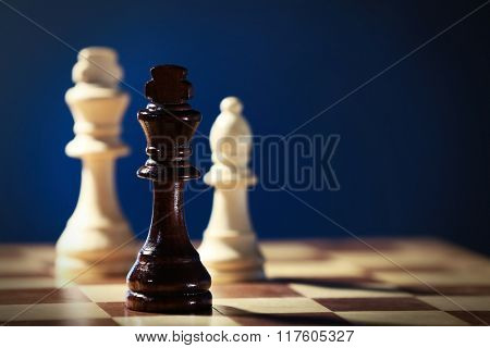 Chess pieces and game board on blue background