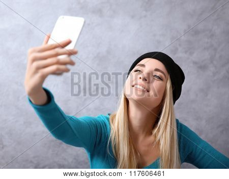 Young girl in black hat taking photo of her self with smart phone on grey wall background