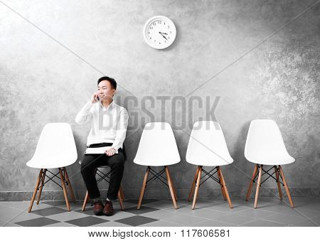Young Asian businessman sitting on a chair in grey hall