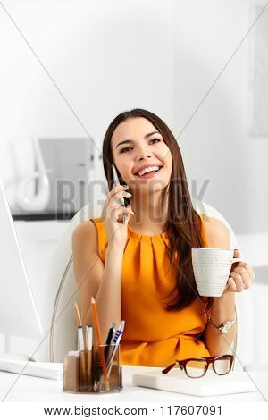 A beautiful successful woman talking on phone and drinking coffee at the modern office