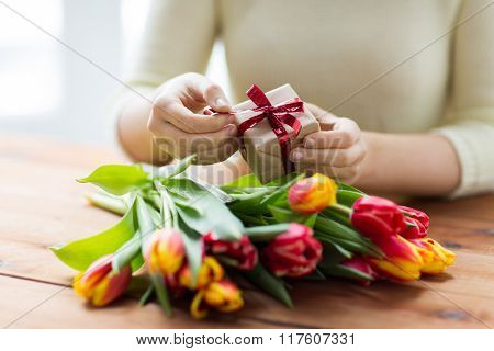 people, holidays and greeting concept - close up of woman holding gift box and tulip flowers