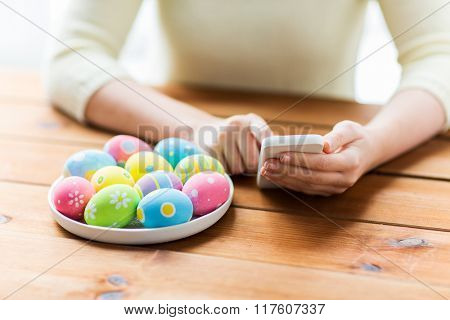 easter, holidays, tradition, technology and people concept - close up of woman hands with colored easter eggs on plate and smartphone