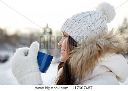 people, season, drinks and leisure concept - happy young woman with tea cup outdoors in winter