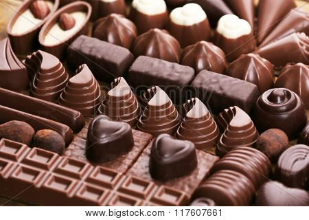 Assortment of delicious chocolate candies background, close up