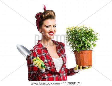Pin-up girl holding flower pot with yellow daisies and shovel