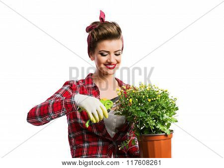 Pin-up girl holding flower pot with yellow daisies and shears