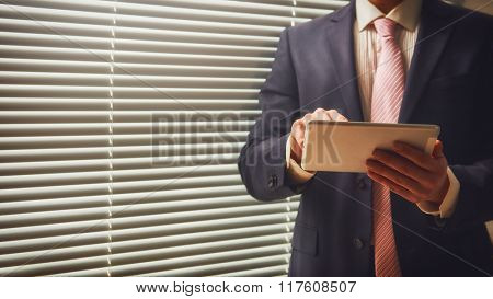 Portrait of a confident man. Entrepreneur working on digital tablet while standing in modern office interior. Intelligent male lawyer working on touch pad.