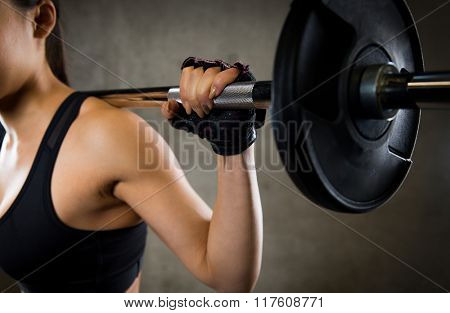 sport, fitness, bodybuilding, weightlifting and people concept - close up of young woman with barbell flexing muscles in gym