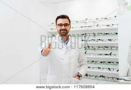 health care, people, eyesight and vision concept - smiling man optician in glasses and white coat showing thumbs up gesture at optics store
