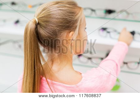 health care, people, eyesight and vision concept - close up of little girl choosing glasses at optics store