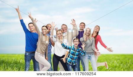 family, gender, generation and people concept - group of smiling men, women and boy having fun and waving hands over blue sky and grass background