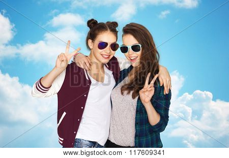 people, friendship, fashion, summer and teens concept - happy smiling pretty teenage girls in sunglasses showing peace hand sign over blue sky and clouds background