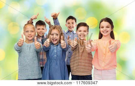 childhood, fashion, gesture and people concept - happy smiling children showing thumbs up over green lights background