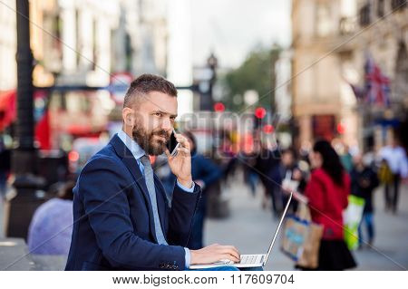 Manager with laptop and smart phone, sunny Piccadilly Circus, Lo