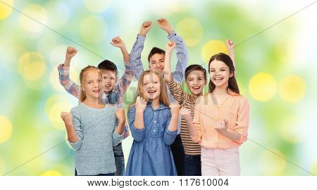 childhood, fashion, gesture and people concept - happy children friends raising fists and celebrating victory over green lights background