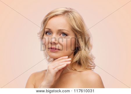 beauty, people and skincare concept - smiling woman with bare shoulders touching face over beige background