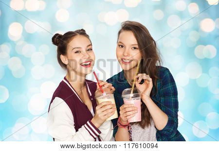 people, friends, teens and friendship concept - happy smiling pretty teenage girls drinking milk shakes and with straw over blue holidays lights background