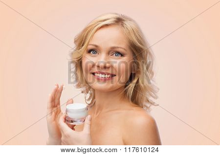 beauty, people, skincare and cosmetics concept - happy woman applying cream to her face over beige background
