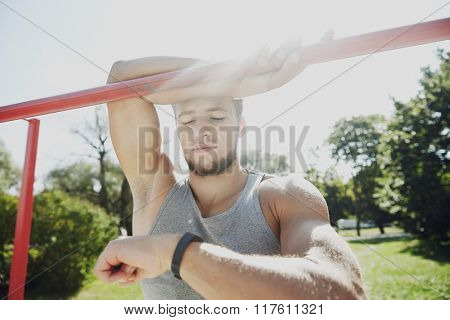 fitness, sport, training and lifestyle concept - happy young man looking at heart-rate watch bracelet and exercising on horizontal bar in summer park