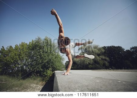 fitness, sport, parkour and people concept - young man jumping in summer park