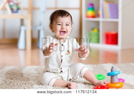 Cute young girl baby playing home with colorful toys