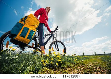 Young lady with bicycle on a spring meadow with flowers
