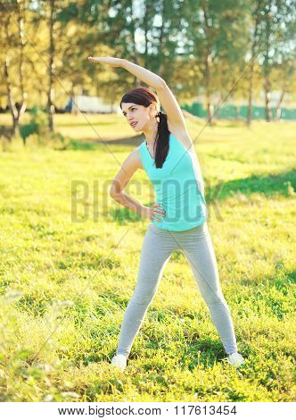 Fitness Woman Doing Stretching Exercises On Grass In Sunny Summer Day