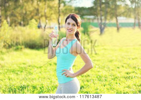 Sport And Fitness Concept - Beautiful Smiling Young Woman Drinking Water From Bottle