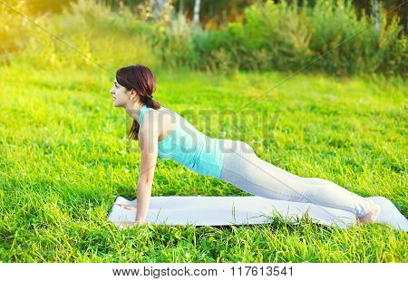 Woman Doing Yoga Exercises On Grass In Summer