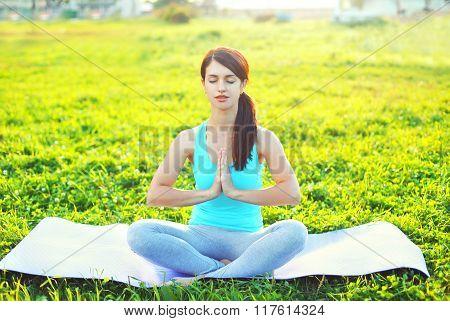 Yoga Woman Meditates Sitting On Grass Pose Lotus In Summer Day