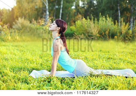 Young Woman Doing Yoga Exercises On Grass In Summer